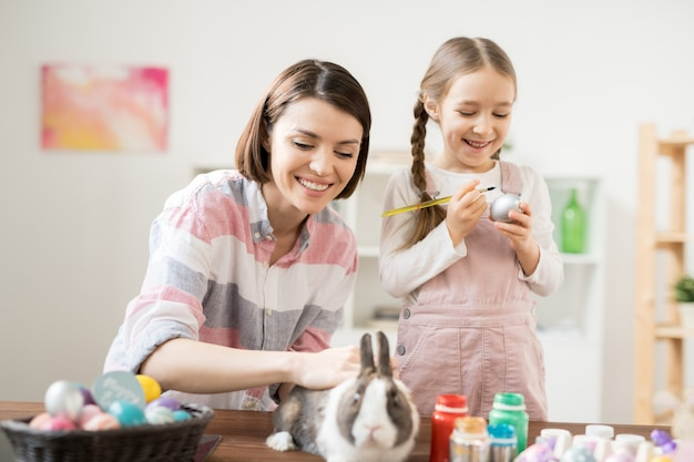 Glückliche junge frau, die niedlichen osterhasen kuschelt, während ihre kleine tochter eier für urlaub malt