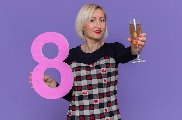 Glückliche junge frau, die nummer acht und glas champagner hält