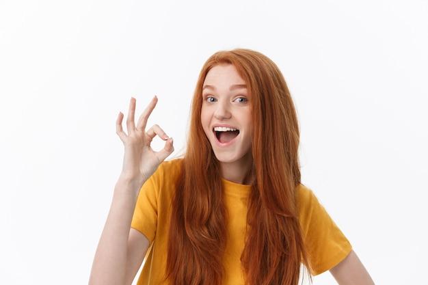 Glückliche junge frau, die ok zeichen mit den fingern ein zwinkern zeigt