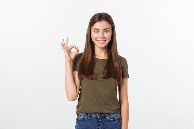Glückliche junge frau, die okayzeichen mit den fingern ein blinzeln lokalisiert auf einem grauen hintergrund zeigt.