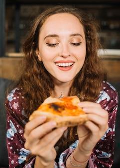 Glückliche junge frau, die pizzascheibe hält