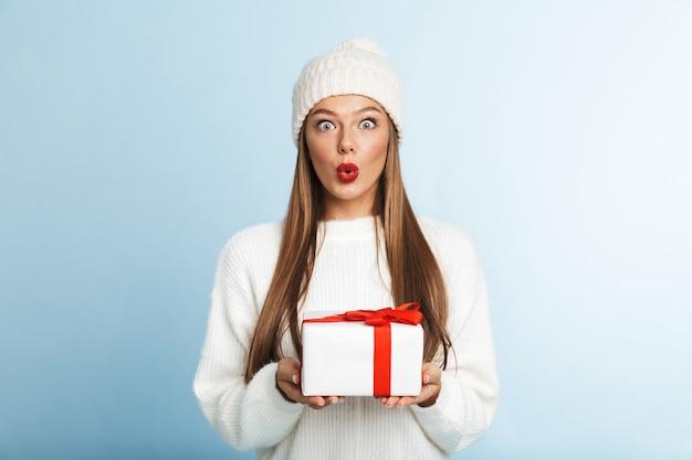 Glückliche junge frau, die pullover hält geschenkbox trägt