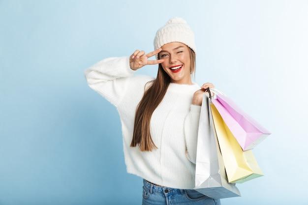 Glückliche junge frau, die pullover trägt, einkaufstaschen trägt, friedensgeste zeigt
