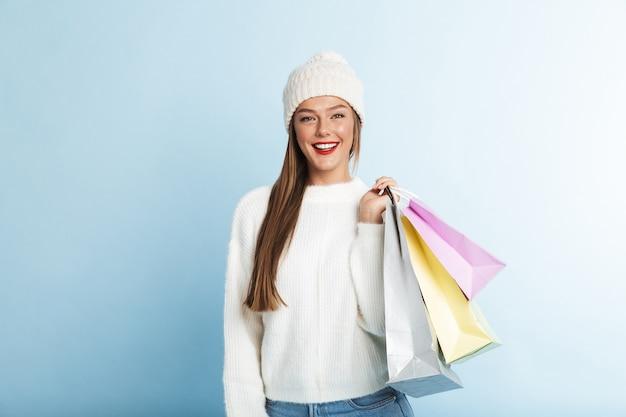 Glückliche junge frau, die pullover trägt und einkaufstaschen trägt