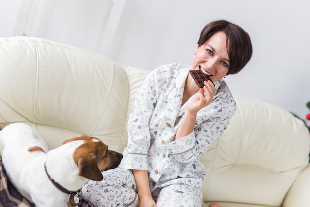 Glückliche junge frau, die pyjama im wohnzimmer mit weihnachtsbaum trägt