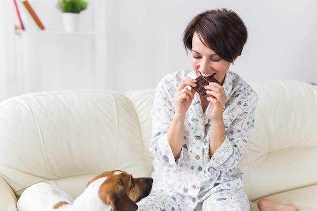 Glückliche junge frau, die pyjama mit reizendem hund im wohnzimmer mit weihnachtsbaum trägt. ferien