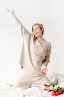 Glückliche junge frau, die pyjamas trägt, die auf dem bett tanzen, das spaß hat