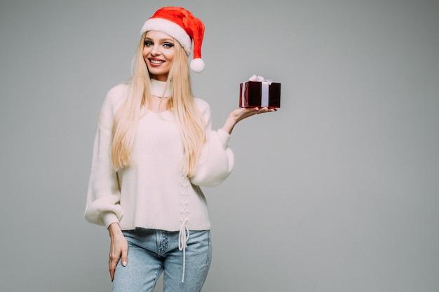Glückliche junge frau, die rote weihnachtsmütze trägt und geschenkbox hält