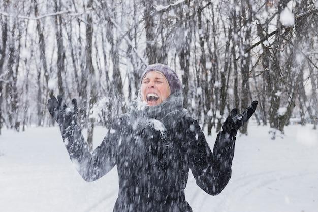 Glückliche junge frau, die schneefälle am winterwald genießt