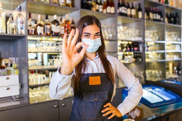 Glückliche junge frau, die schützende gesichtsmaske im restaurant während der coronavirus-pandemie trägt, barkeeper, der ok zeichen zeigt. regale voller flaschen mit alkohol auf dem hintergrund