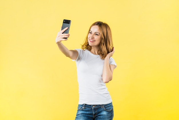 Glückliche junge frau, die selfie am handy gegen gelben hintergrund nimmt