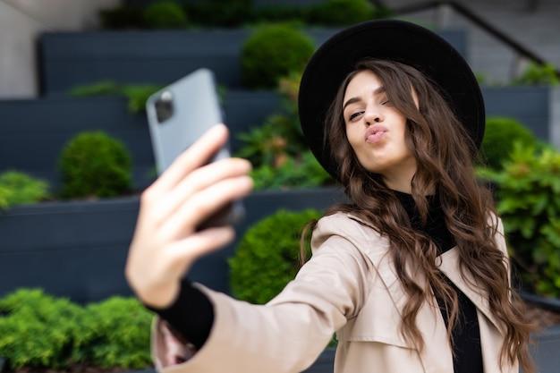 Glückliche junge frau, die selfie mit entengesicht auf stadtstraße nimmt