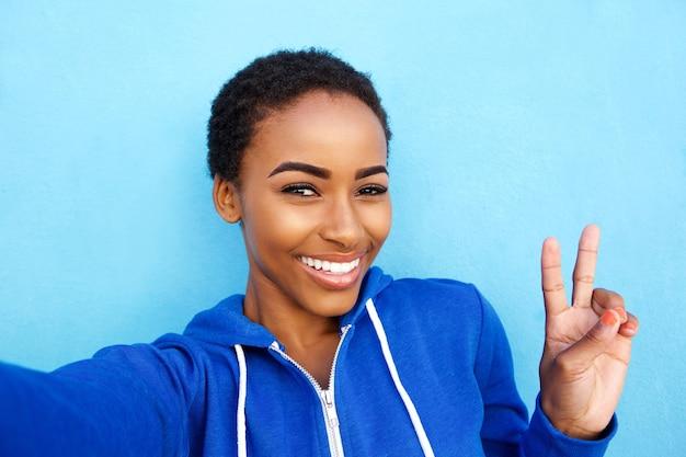 Glückliche junge frau, die selfie mit friedenshandzeichen nimmt