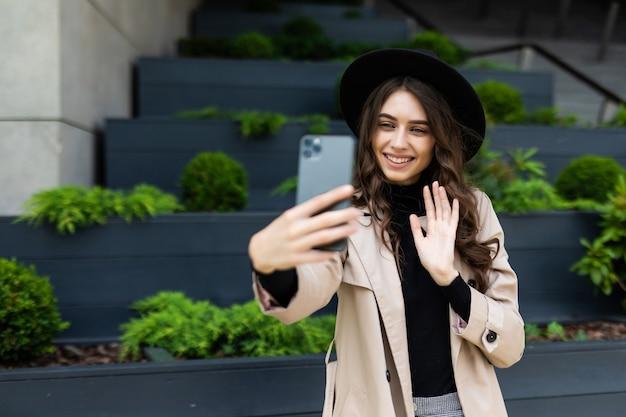 Glückliche junge frau, die selfie mit friedenszeichen auf stadtstraße nimmt