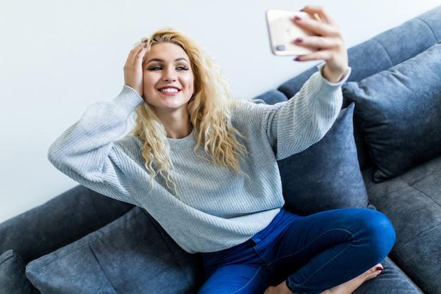 Glückliche junge frau, die selfie mit ihrem telefon beim sitzen im wohnzimmer nimmt.