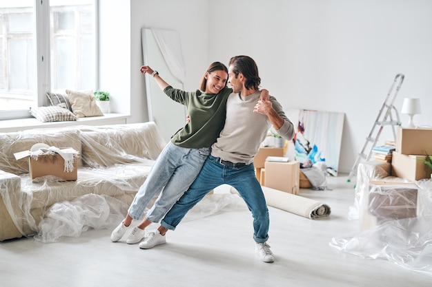 Glückliche junge frau, die sich auf ihren ehemann stützt, während beide im wohnzimmer voller gepackter sachen tanzen, nachdem sie in eine neue wohnung oder ein neues haus umgezogen sind