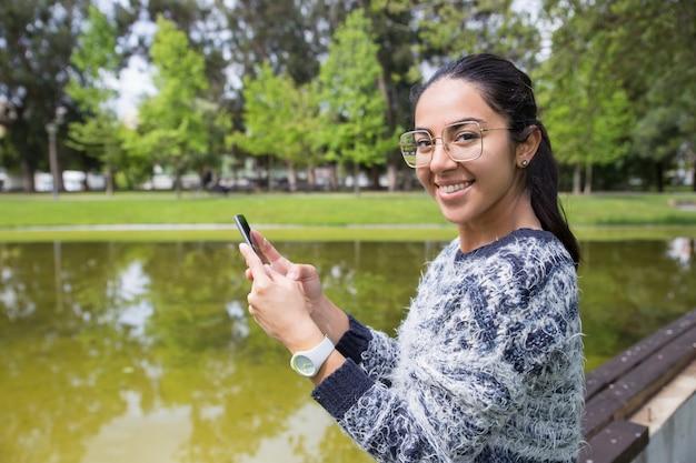 Glückliche junge frau, die smartphone im park verwendet
