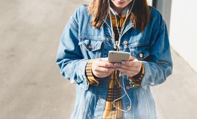 Glückliche junge frau, die social media auf ihren smartphones gehen hinunter eine stadtstraße verwendet