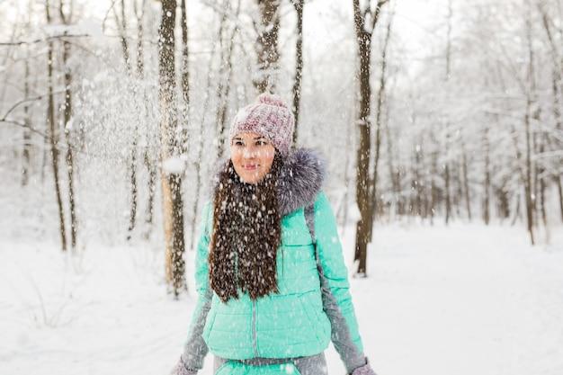 Glückliche junge frau, die spaß im schnee hat.