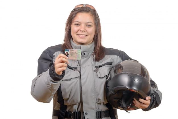 Glückliche junge frau, die stolz ihren neuen motorradschein zeigt