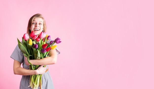 Glückliche junge frau, die strauß der frischen tulpen lokalisiert auf rosa hintergrund hält