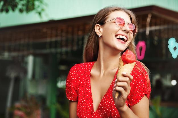 Glückliche junge frau, die süßigkeiten in den sommerferien isst