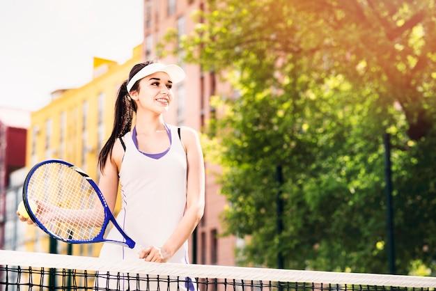 Glückliche junge frau, die tennis auf dem gericht spielt