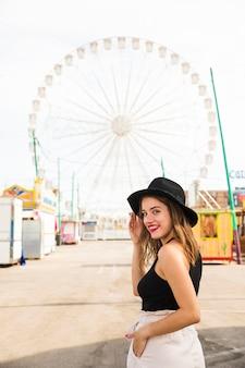 Glückliche junge frau, die über schulter mit ihrer hand in der tasche am vergnügungspark schaut