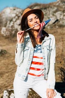 Glückliche junge frau, die usa-flagge beißt