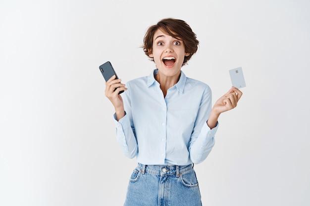 Glückliche junge frau, die vor freude schreit und handy mit plastikkreditkarte hält, stehend auf weißer wand