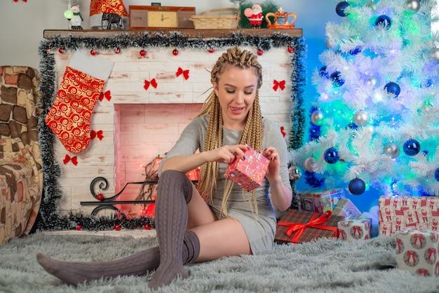 Glückliche junge frau, die weihnachtsgeschenkbox nahe kamin hält, verzierte weihnachtsbaum