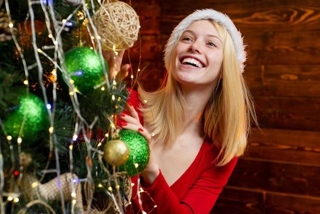 Glückliche junge frau, die weihnachtskugel vor weihnachtsbaum hält. schönheitsmädchen, das verziert