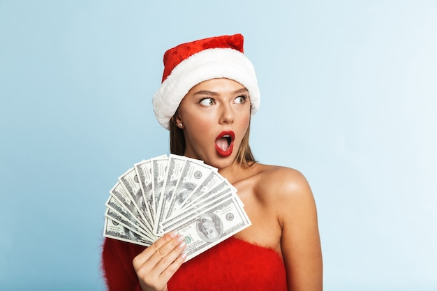 Glückliche junge frau, die weihnachtsmütze trägt und geld hält.