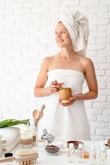 Glückliche junge frau, die weiße bademänteltücher auf kopf trägt, die spa-prozeduren tun, die natürliche zutaten im spa-schönheitssalon mischen