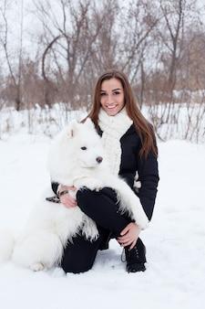 Glückliche junge frau, die weißen samojedenhund auf schnee streichelt