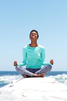 Glückliche junge frau, die yoga am strand tut