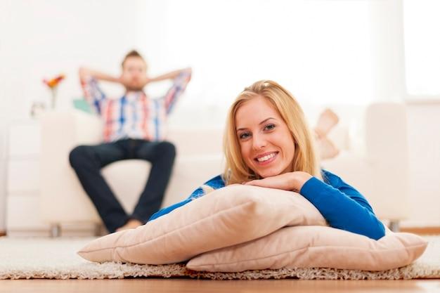 Glückliche junge frau, die zu hause auf teppich liegt