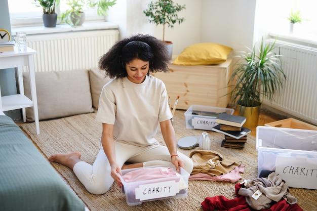 Glückliche junge frau, die zu hause garderobe sortiert, spendenkonzept für wohltätige zwecke.