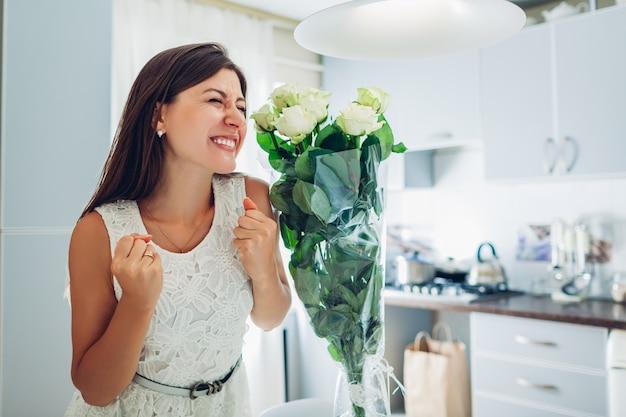 Glückliche junge frau fand blumenstrauß von rosenblumen auf küche