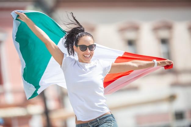 Glückliche junge frau feiert den sieg italiens auf einer straße, die eine flagge hält und vor freude springt.