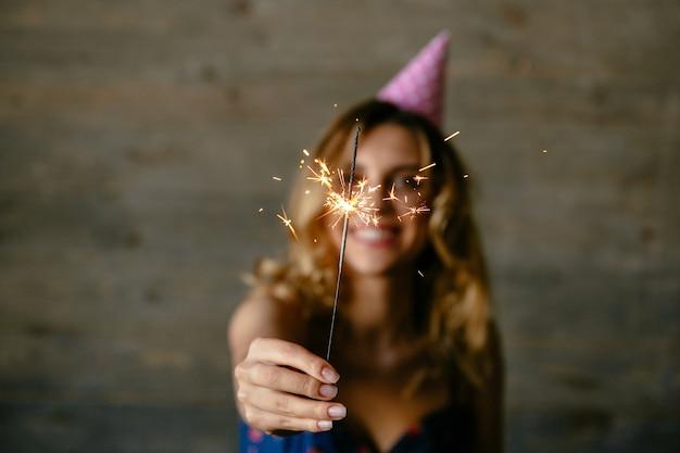 Glückliche junge frau hält das fokussierte bengal-licht und feiert den feiertag