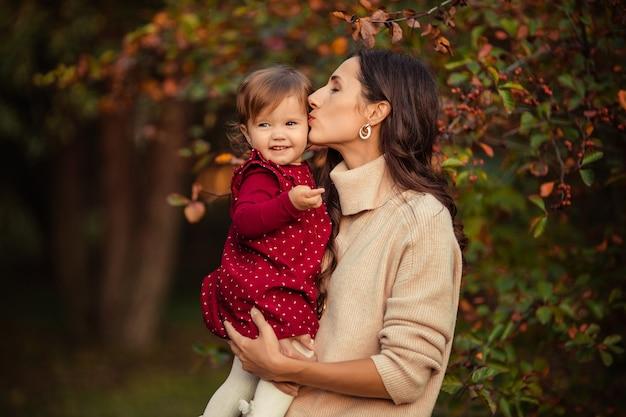 Glückliche junge frau hält ihre kleine tochter in ihren armen