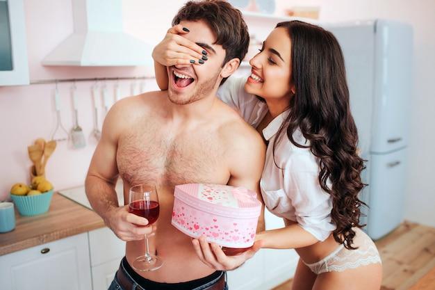 Glückliche junge frau halten seine augen geschlossen. sie gibt dem kerl ein geschenk. junger mann hat ein glas wein in der hand. sie stehen in der küche.