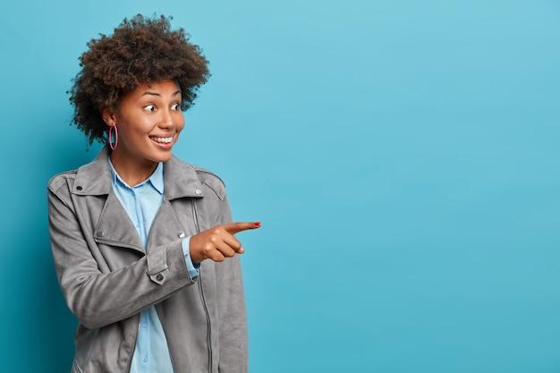 Glückliche junge frau hilft bei der auswahl der besten wahl, empfiehlt produkt, trägt stilvolle kleidung, hat positiven ausdruck überrascht, modelle