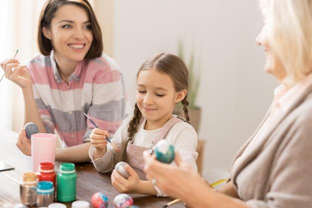 Glückliche junge frau, ihre tochter und mutter, die eier für ostern mit bunter gouache vor dem feiertag malen