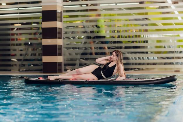 Glückliche junge frau im bikini sonnt sich auf einem surfbrett im poollehrer an einer indoor-surffac...