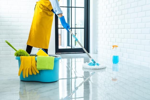 Glückliche junge frau im blauen gummi mit mopp beim reinigen auf boden zu hause