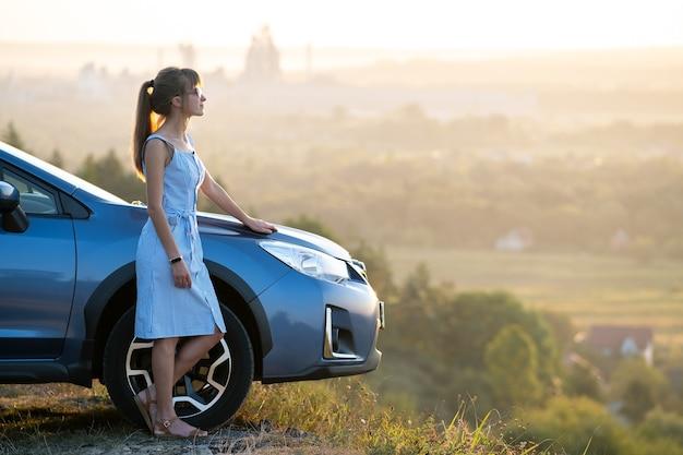 Glückliche junge frau im blauen kleid, das nahe ihrem fahrzeug steht, das sonnenuntergangansicht der sommernatur betrachtet. reise- und urlaubskonzept.
