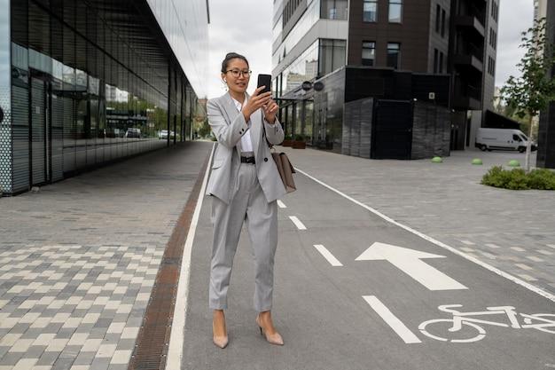 Glückliche junge frau im eleganten anzug macht selfie auf der straße