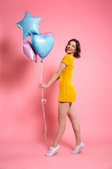 Glückliche junge frau im gelben kleid, das ballons hält